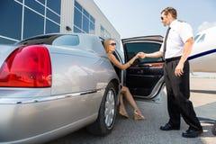 Piloto Helping Woman Stepping fuera del coche en Imagenes de archivo