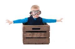 Piloto joven del muchacho que vuela una caja de madera Fotos de archivo libres de regalías