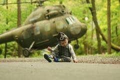 Piloto joven El concepto de la opción de la profesión Bebé en el casco experimental con los vidrios en la carretera de asfalto Foto de archivo libre de regalías