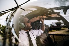 Piloto ligando os controles no helicóptero imagens de stock royalty free
