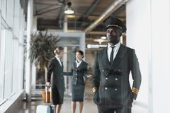 piloto novo pensativo no aeroporto com comissárias de bordo foto de stock