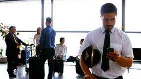Piloto que usa el teléfono móvil mientras que viajeros que obran recíprocamente con uno a metrajes