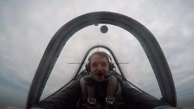 Piloto sonriente que se sienta en la carlinga de un avión aeroacrobacia ligero, emociones del vuelo, acrobacias aéreas metrajes