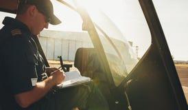Piloto verificando o manual do voo antes de uma descolagem Fotografia de Stock