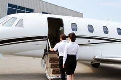 Piloto y azafata que entran en el jet privado Imagen de archivo
