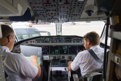 Pilotos na cabina do piloto de aviões Imagens de Stock