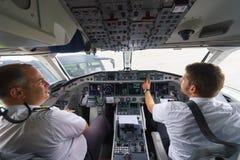 Pilotos na cabina do piloto de aviões Fotos de Stock