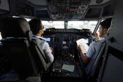 Pilotos na cabina do piloto de aviões de passageiro foto de stock