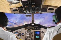 Pilotos na cabina do piloto e no por do sol planos Fotografia de Stock