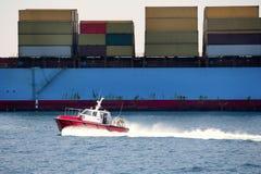 Pilotos portuarios del barco comparados al contenedor para mercancías Foto de archivo