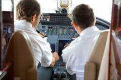 Pilotos que operam controles do jato incorporado fotografia de stock