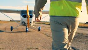 Pilotowy iść na pasie startowym, tylny widok Profesjonalisty pilotowy przybycie jego samolot, chodzi na lotnisku zdjęcie wideo