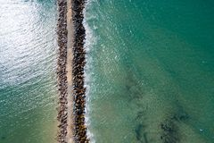 Pilots Beach Breakwall. Breakwalls can seem like just a big pile of stones, but looking from above and playing with composition, light and texture suddenly they Royalty Free Stock Image