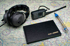 Pilots equipment before the flight. Headphones, fuel sampler, radio and log book Stock Photography