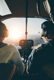 Pilots flying a helicopter on sunny day Stock Photography
