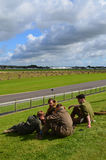 Pilots at the Goodwood Aerodrome marking the 75th Battle of Britain anniversary. Young men dressed in WW2 aircrew clothing sit on the grass banks around the Stock Images