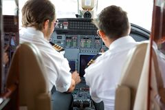 Pilots Operating Controls Of Corporate Jet. Rear view of pilot and copilot operating controls of corporate jet stock photography