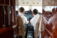 Pilots Operating Controls Of Private Jet. Rear view of pilot and copilot operating controls of private jet Royalty Free Stock Photo