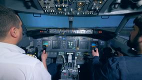 The plane takes off, pilots are in the cockpit. Pilots sit in a plane simulator cockpit, while the plane takes off stock video footage