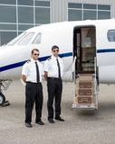 Pilots Standing By Private Jet. Full length of mid adult pilots standing by private jet with open door Royalty Free Stock Images