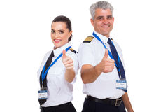 Pilots thumbs up. Cheerful airline pilots giving thumbs up over white background Royalty Free Stock Photos