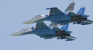 Pilots of two military aircraft SU27 jointly perform a turn. Pilots of two military aircraft SU27 of the pilot group `Russian Knights` jointly perform a figure Royalty Free Stock Photo