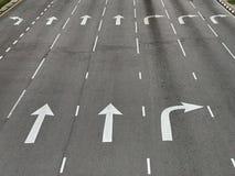 Pilriktningar på asfaltvägen på en föreningspunkt royaltyfria bilder