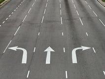 Pilriktningar på asfaltvägen på en föreningspunkt royaltyfri fotografi
