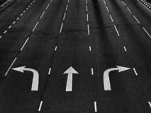 Pilriktningar på asfaltvägen på en föreningspunkt i svartvitt royaltyfri foto