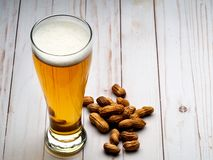 Pilsner beer and peanuts. Pilsner of light beer with peanuts on light wooden table stock photos