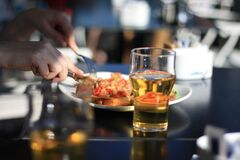Pilsner Glass With Beer Beside White Plate Royalty Free Stock Photos