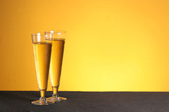 Pilsner pastime with copy space. Two pilsner glasses on a golden backdrop with copy space stock photography