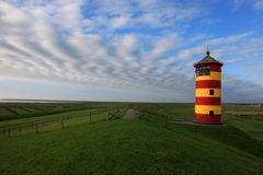 Pilsum Greetsiel light house. Photo shows a nice colorful red and yellow beacon on a dike. around is the big fresh green grass meadow and a long way with nice stock photos