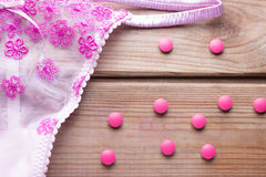 Pilule contraceptive et lingirie rose Photographie stock
