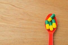 Pilule de capsule de médecine sur la cuillère Photographie stock libre de droits