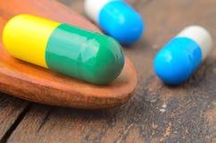 Pilule de capsule de médecine sur la cuillère, fond en bois Image libre de droits