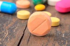 Pilule de capsule de médecine sur le fond en bois Photos stock