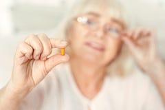Pilule retirée curieuse de visionnement de femme à la maison Photo stock