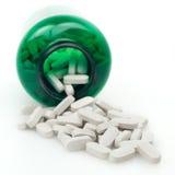 Pilules avec la bouteille verte de médecine sur le fond blanc Photos libres de droits