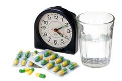 Pilules avec le verre de l'eau et du réveil Photos stock