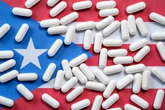 Pilules blanches de prescription sur le fond de drapeau du Porto Rico Photos stock