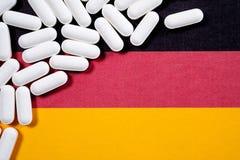 Pilules blanches sur le drapeau allemand Image stock