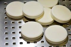 Pilules blanches sur le fond d'acier inoxydable photos libres de droits