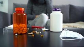Pilules, capsules et thermomètre sur la table Femme prenant le médicament banque de vidéos