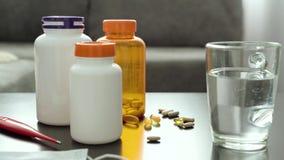 Pilules, capsules, thermomètre et un verre de l'eau sur la table banque de vidéos