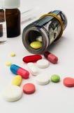 Pilules colorées avec l'argent La santé coûte beaucoup Photo stock