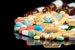 Pilules colorées d'isolement sur le blackbackground Image stock
