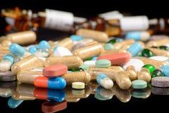 Pilules colorées d'isolement sur le blackbackground Photos stock