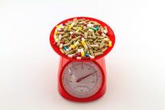 Pilules colorées dans l'échelle rouge de poids Images libres de droits