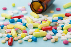 Pilules colorées de drogue sur le fond bleu Photo libre de droits